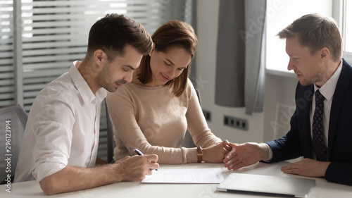 Fotografía Young couple making deal with manager, signing contract