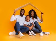 Black Family Sitting Under Symbolic Roof Dreaming Of New Home.
