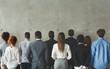 Businesspeople looking at grey wall with free space