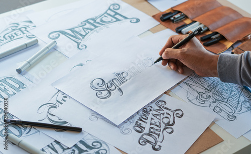 Foto Typography Calligraphy artist designer drawing sketch writes letting spelled pen brush ink paper table artwork
