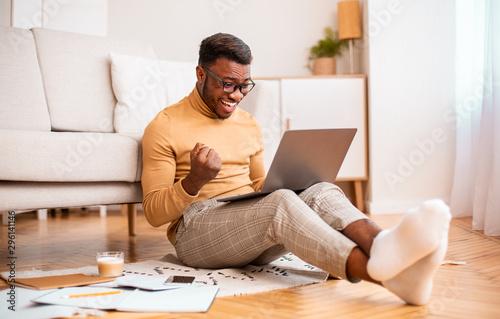 Valokuvatapetti Excited Black Guy Using Laptop Shaking Fists Sitting At Home