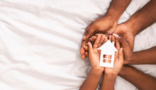 Black Family Of Three Holding Paper House Figure In Hands