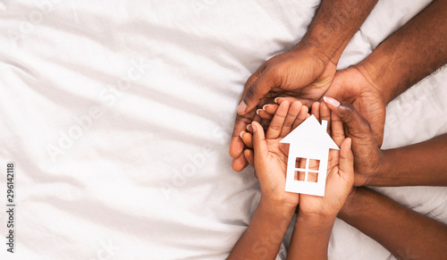 Foto  Black family of three holding paper house figure in hands