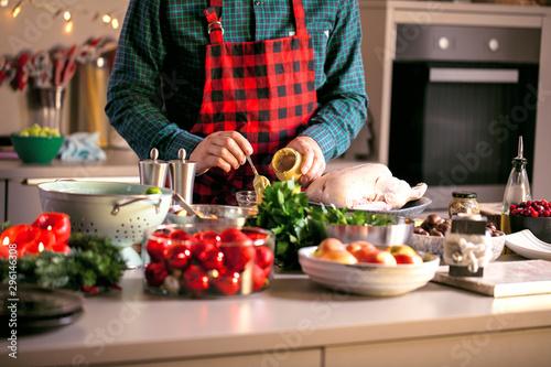 Fototapeta Mann bereitet leckeres und gesundes Essen in der häuslichen Küche zu Weihnachten zu (Weihnachtsente oder gans) obraz