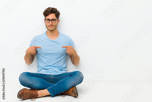 Obraz young handsome man looking proud, positive and casual pointing to chest with both hands sitting on the floor - fototapety do salonu