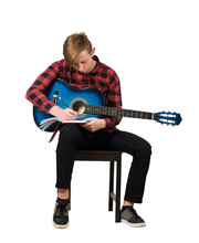 Full Length Portrait Of Talented Boy Music Composer With His Trendy Acoustic Guitar Seated On Chair Thinking To Write A New Song With Chords In His Notebook Isolated Over White Background.
