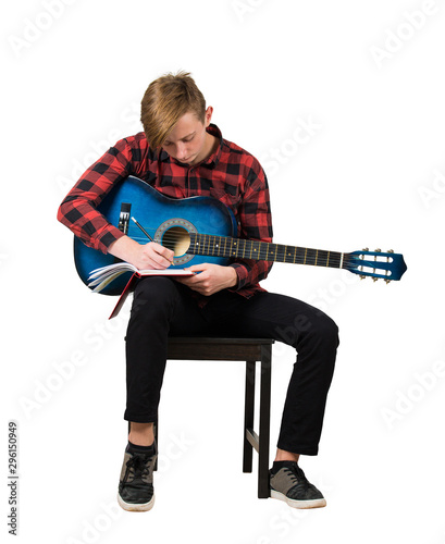 Fotomural  Full length portrait of talented boy music composer with his trendy acoustic guitar seated on chair thinking to write a new song with chords in his notebook isolated over white background