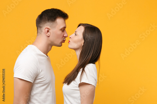 Pretty young couple two friends guy girl in white empty blank design t-shirts posing isolated on yellow orange background Fototapeta