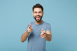 Young cheerful handsome man in casual clothes posing isolated on blue wall background, studio portrait. People sincere emotions lifestyle concept. Mock up copy space. Pointing index fingers on camera.
