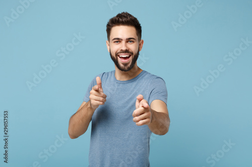 Obraz Young cheerful handsome man in casual clothes posing isolated on blue wall background, studio portrait. People sincere emotions lifestyle concept. Mock up copy space. Pointing index fingers on camera. - fototapety do salonu