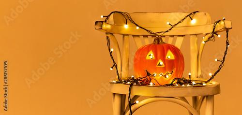 Orange pumpkin with garland lights on chair Canvas Print