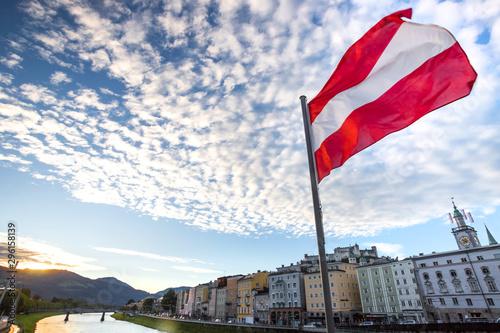 Fényképezés austrian flag over historic salzburg cityscape