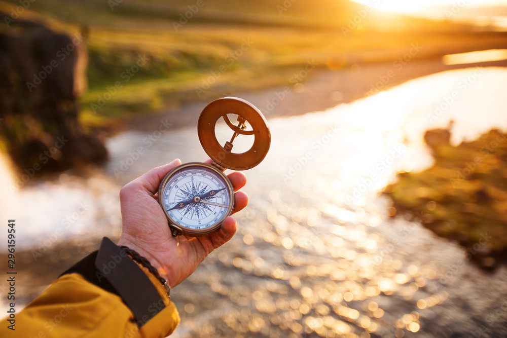 Fototapeta Beautiful landscape with old compass on traveler's hand. Traveling concept.