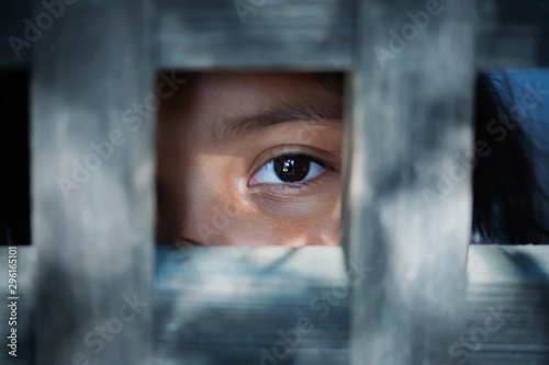The blank stare of a child's eye who is standing behind what appears to be a wooden cage to convey captivity, or bondwoman Wallpaper Mural