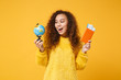 Excited young african american girl in fur sweater posing isolated on yellow orange wall background. People lifestyle concept. Mock up copy space. Holding world globe, passport, boarding pass tickets.