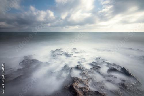 Foto auf Gartenposter Dunkelgrau Idyllic rocks bathed by an ethereal sea under a spectacular cloudscape