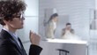 Close up of intelligent businesswoman tapping on invisible multi-touch interface on glass wall and reading on virtual screen in office. Video suitable for adding AR graphics