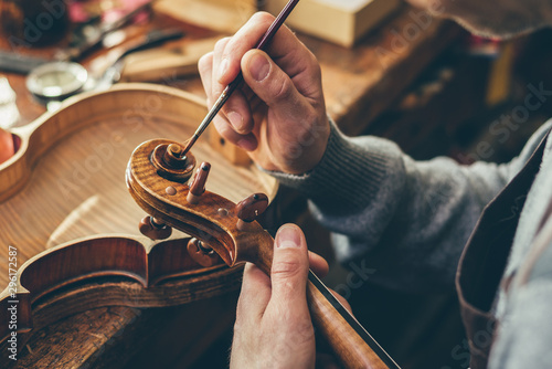Fototapeta Luthier repair violin in his workshop