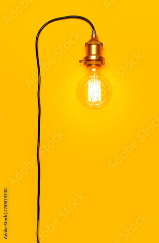 Vintage fashionable edison lamp on bright yellow background. Top view flat lay copy space. Creative idea concept, designer lamp, modern interior item. Lighting, electricity, background with lamp
