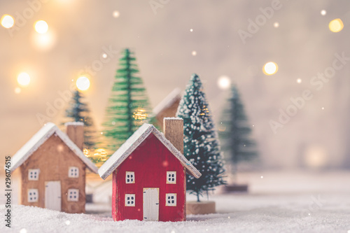 Miniature wooden houses on the snow over blurred Christmas decoration background, toned, postcard concept