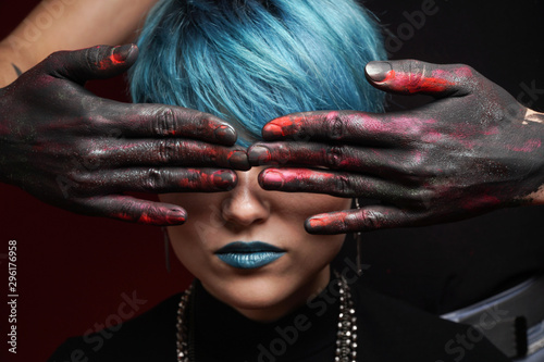 Eyes of beautiful girl with short blue fashionable hairstyle and blue lipstick covered by men's hands in black, pink and red paint on a dark background. See no evil concept. Close-up studio photo