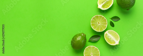 Fresh juicy lime and green leaves on bright green background. Top view flat lay copy space. Creative food background, tropical fruit, vitamin C, citrus. Composition with whole and slices of lime - 296179130
