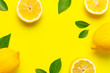 canvas print picture - Creative background with fresh lemons and green leaves on bright yellow background. Top view flat lay copy space. Lemon fruit citrus minimal concept vitamin C. Composition with whole, slices of lemons