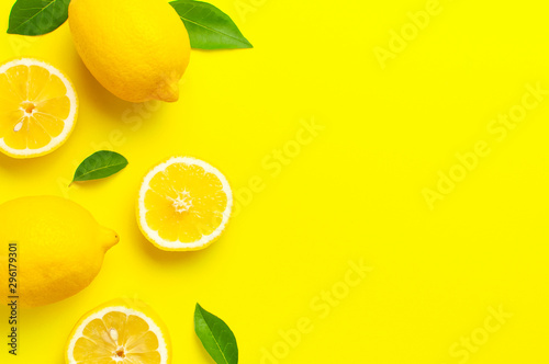 Creative background with fresh lemons and green leaves on bright yellow background Tapéta, Fotótapéta