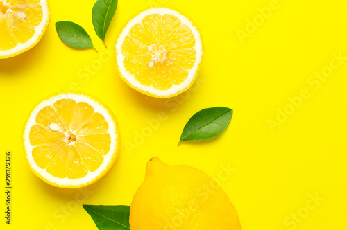 Creative background with fresh lemons and green leaves on bright yellow background. Top view flat lay copy space. Lemon fruit citrus minimal concept vitamin C. Composition with whole, slices of lemons - 296179326