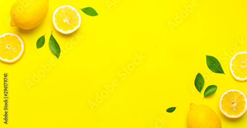 Canvastavla Creative background with fresh lemons and green leaves on bright yellow background