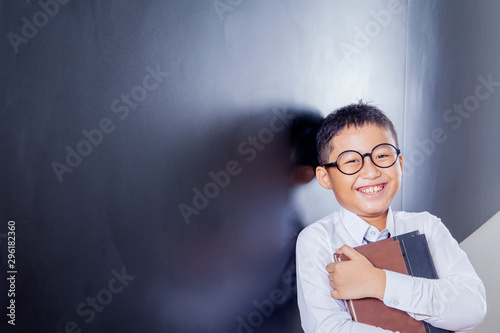 Happy schoolboy holding a book in the classroom Wallpaper Mural