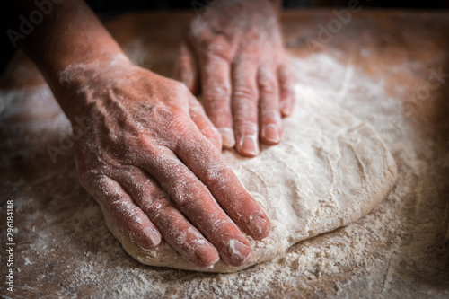 Poster de jardin Boulangerie Making dough by female hands on wooden table background close up