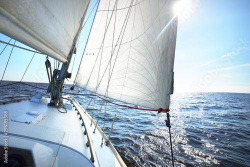 Garden Poster Sailing White sloop rigged yacht sailing in an open Baltic sea on a clear sunny day. A view from the deck to the bow, mast and sails. Estonia