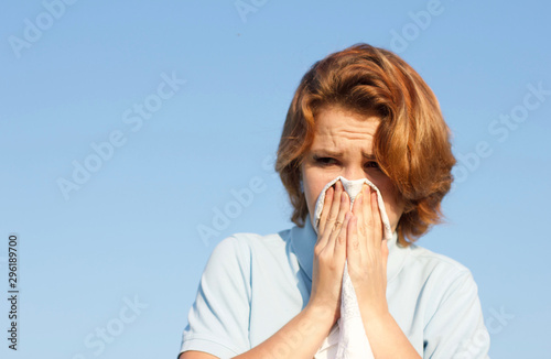 Photo Young woman blowing her nose into handkerchief or tissue at summer sunny hot day