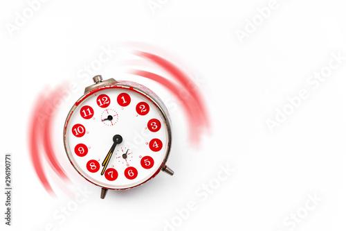 Reloj despertador vintage de color rojo sonando sobre fondo blanco