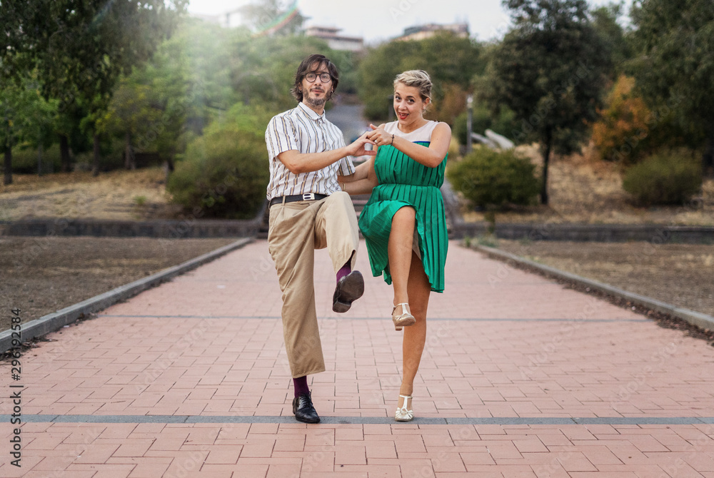 Fototapety, obrazy: Swing dancers having fun outdoors in the park. Lifestyle concept about people dancing swing music Lindy hop together and having fun!