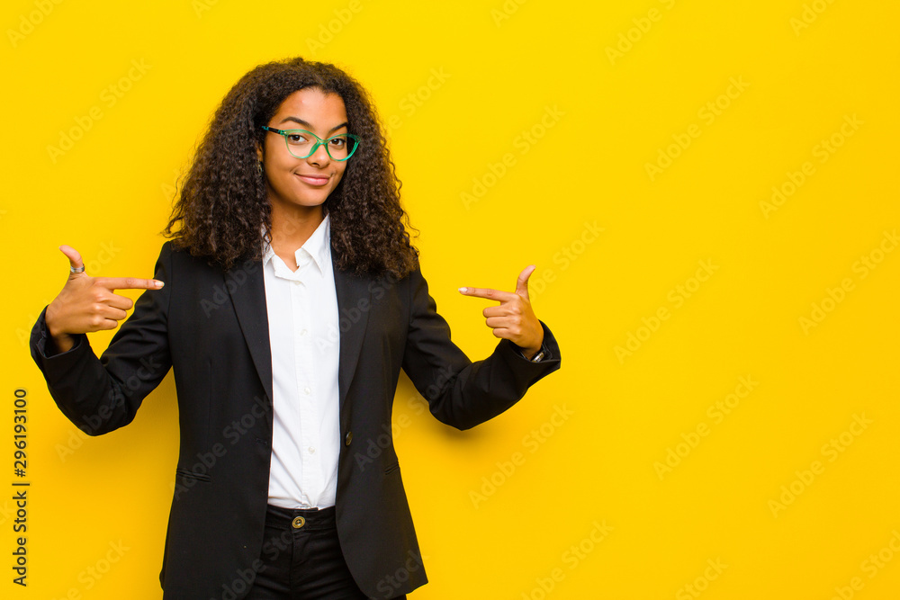 Fototapety, obrazy: black business woman looking proud, arrogant, happy, surprised and satisfied, pointing to self, feeling like a winner against orange wall