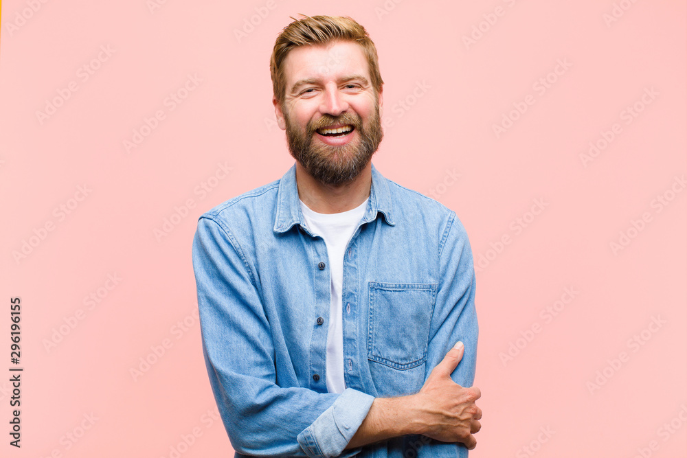 Fototapeta young blonde adult man laughing shyly and cheerfully, with a friendly and positive but insecure attitude