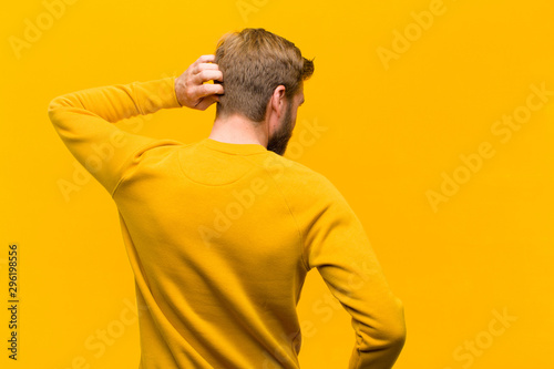 Fotomural  young blonde man thinking or doubting, scratching head, feeling puzzled and conf