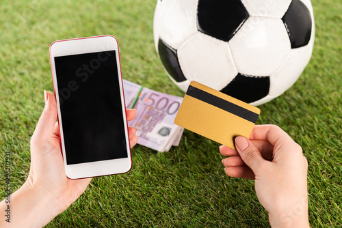 fototapeta na szkło cropped view of female hands with smartphone and credit card near soccer ball and euro banknotes on green grass, sports betting concept