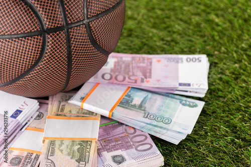 Foto op Canvas Londen close up view of basketball ball near dollar and euro banknotes on green grass, sports betting concept