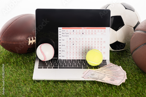 Obraz na plátne laptop near sports balls and betting list on green grass isolated on white, spor