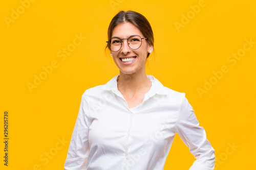 young businesswoman smiling happily with a hand on hip and confident, positive, proud and friendly attitude against orange wall