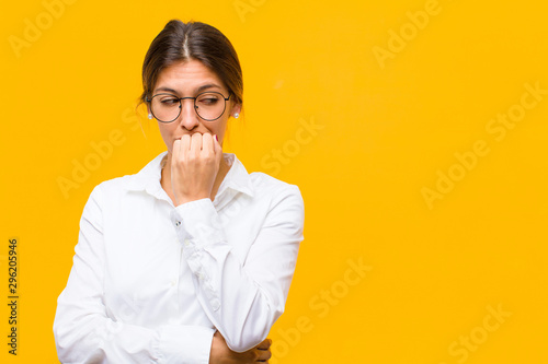 Fotomural  young businesswoman feeling serious, thoughtful and concerned, staring sideways