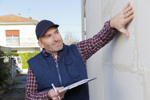 A Builder Inspecting A House