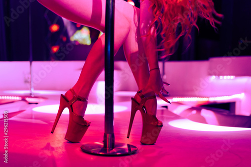Tuinposter Ezel Heels of sexy woman pole dancing or striptease. Pylon in night club. Stripper girl background