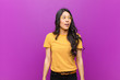 canvas print picture - young pretty latin woman feeling shocked, happy, amazed and surprised, looking to the side with open mouth against purple wall