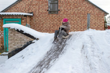 Cheerful Girl Using Plastic Bag As A Sled And Riding Down From Cellar With Icey Trek In Front Of Brick Village House In Winter Day.