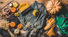 Autumn Trendy Outfit Layout. Flat-lay Of Vintage Denim Jacket, Sweater, Jeans, Woolen Scarf, Hat, Yellow Boots, Pumpkins, Candle And Tea In Cup Over Wooden Background, Top View. Fall Apparel And Mood