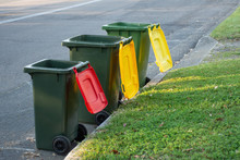 Australian Garbage Wheelie Bins With Colourful Lids For Recycling And General Household Waste Lined Up On The Street Kerbside For Council Rubbish Collection